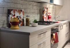 jasne meble kuchenne i kamień na ścianie